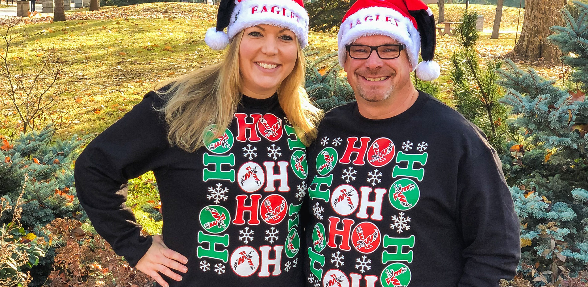 Two people wearing Eagles Holiday Sweaters
